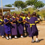 Children dancing outside the new classrooms at IPS Bamali
