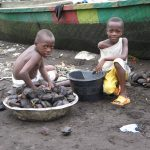 Children collect seed pods on the beach at Limbe